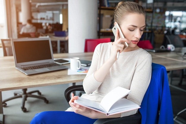 Business woman is sitting in chair and holding notebook. also she is talking on the phone. woman is looking down to the left. she is concentrated on that.