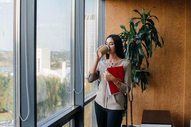 Деловая женщина стоит в офисе возле окна и изучает документы. бизнес, финансы, юрист