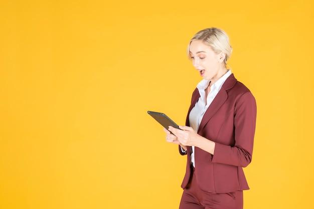 Business woman is surprising  in studio yellow