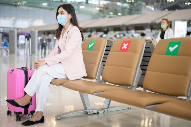 A business woman is wearing protective mask in international airport, travel under covid-19 pandemic, safety travels, social distancing protocol, new normal travel concept