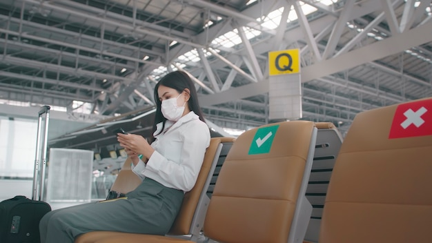 A business woman is wearing protective mask in international airport, travels under covid-19 pandemic