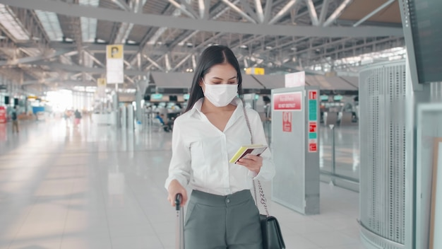 A business woman is wearing protective mask in international airport