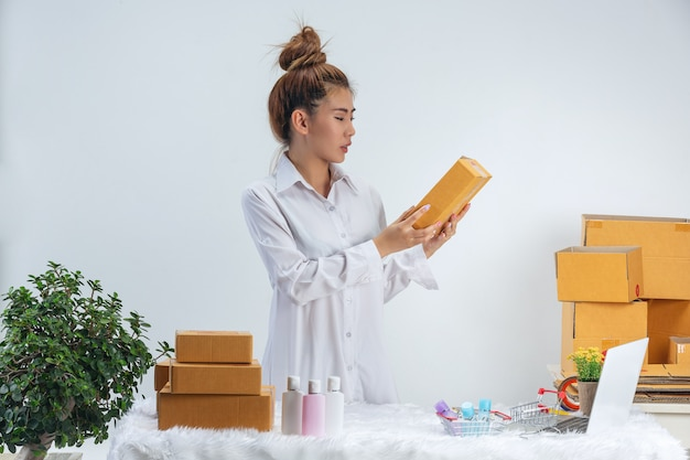 A business woman is working online and traing to reply customer  at home office packaging on wall.