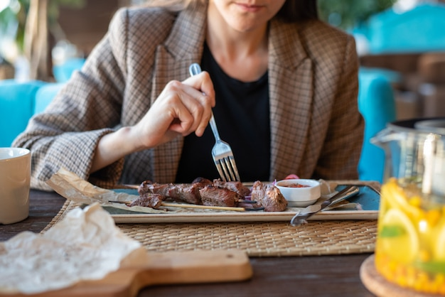 Business woman in jacket close-up in restaurant with cutlery eating grilled meat