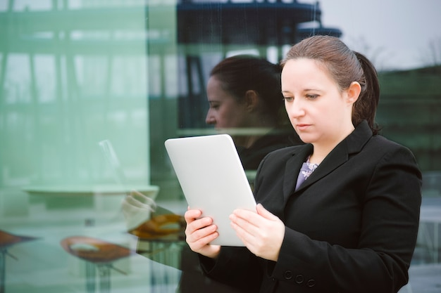 Business woman leaning against a large window of an office building looking at her tablet