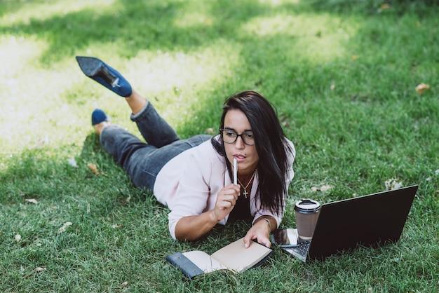 ビジネスウーマンは、ラップトップを使用して、夏の芝生公園に横たわっています。