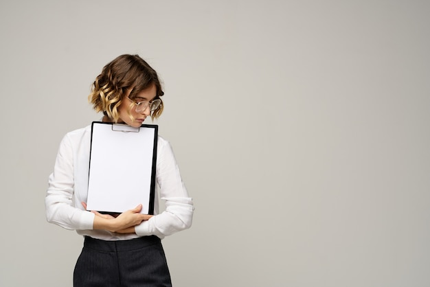 Business woman in a light shirt and a folder with documents