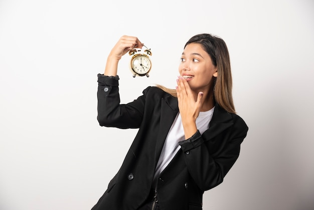 Business woman looking on an alarm clock on white wall.