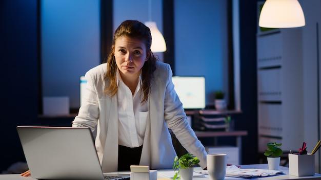 夜遅くにスタートアップ企業の机の近くに立っているラップトップに入力した後、笑顔でカメラを見ているビジネスウーマン。仕事を読むために残業をしているテクノロジーネットワークワイヤレスを使用している集中した従業員。
