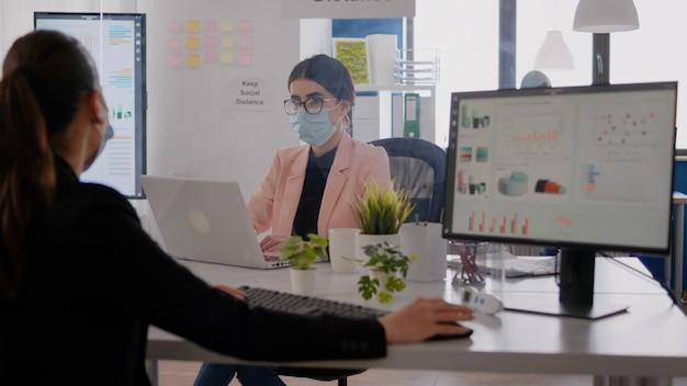 会社のオフィスに座っている同僚と話している間、コンピューターのディスプレイ上の財務グラフを見ているビジネスウーマン。 covid19病を予防するために社会的距離を保つフェイスマスクを持った同僚