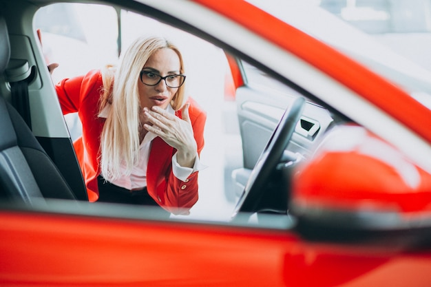 Business woman looking for an auto mobile at a car showroom