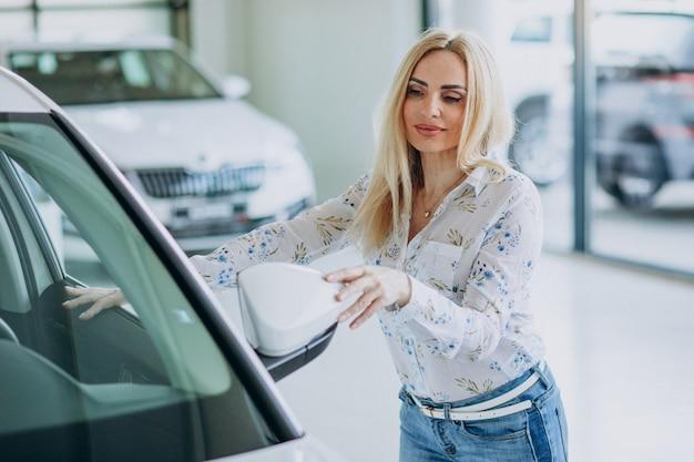 Donna di affari che cerca un cellulare automatico ad una sala d'esposizione dell'automobile
