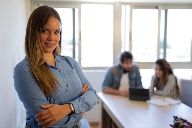 Business woman looking at camera with meeting in background