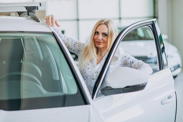 자동차 쇼룸에서 자동 모바일을 찾고 비즈니스 우먼