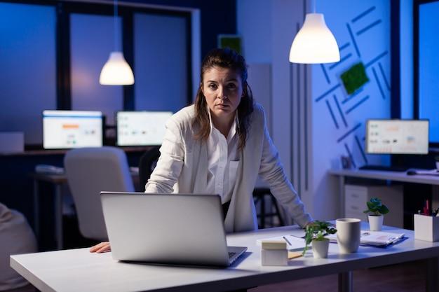 夜遅くにスタートアップ企業の机の近くに立っているカメラに疲れているビジネスウーマン