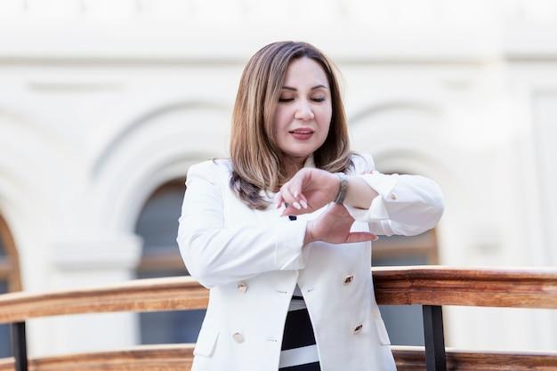ビジネスの女性は彼女の時計を見てください。ビジネスセンターの白いジャケットのブルネット。閉じる。時間管理。