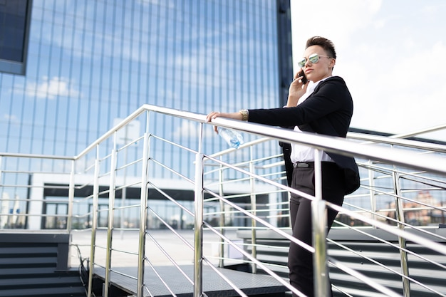 Business woman at the lunch break with a telephone climbs the steps of an office building outside