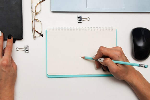 Business woman makes an entry in a notebook on the table