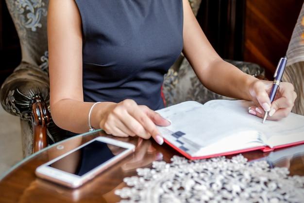 ビジネスウーマンがホームオフィスでノートや日記にメモをとる