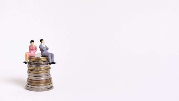 Business woman and man sitting on a pile of coins copy space