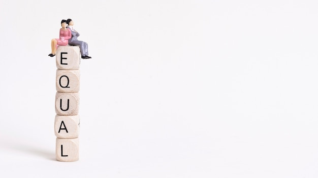 Business woman and man sitting on a pile of wooden cubes copy space