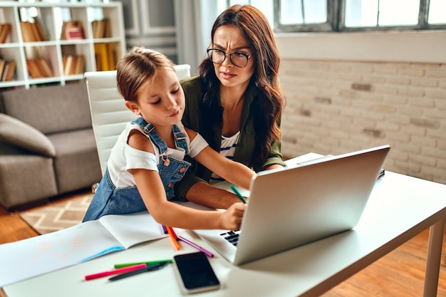 Business woman and mom try to work at the laptop when her little daughter is playing, fooling around and interfering with her. freelance, work from home.