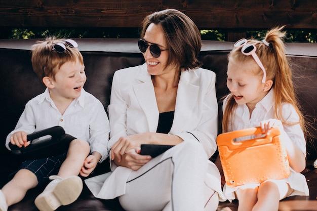 Madre della donna di affari che lavora dalla casa con i bambini
