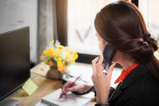 График примечания бизнес-леди на книге и разговаривать с клиентом по телефону.