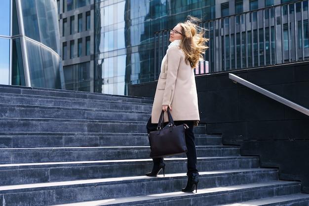 ポルトで白人の外観のビジネスウーマンは、バッグを持ってオフィスビルへの階段を登ります...