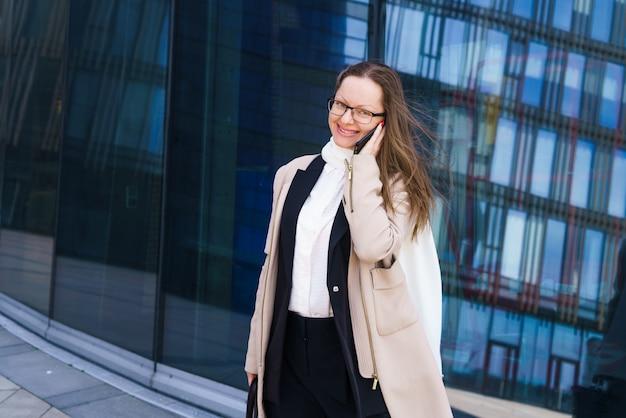 비즈니스 센터 근처 전화 통화 하는 안경을 쓴 백인 민족의 비즈니스 우먼 ...