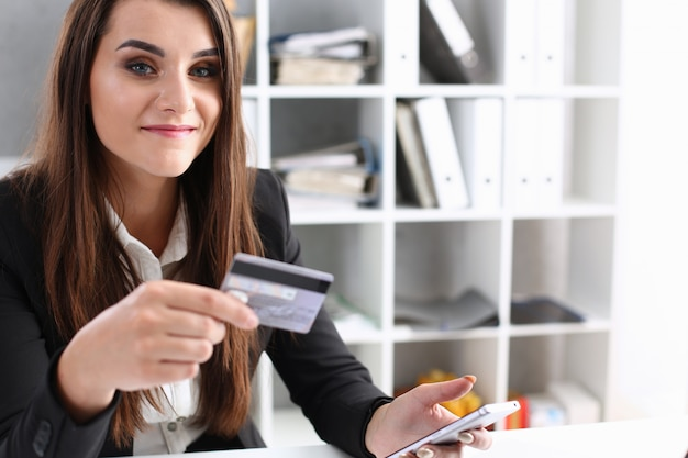 Business woman in the office holds a plastic credit debit card in her hand