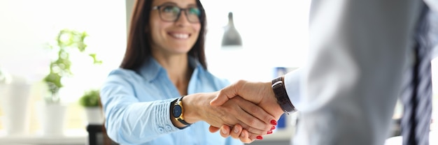Business woman in office shakes hands with business partner.