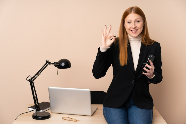 Business woman in a office showing an ok sign with fingers