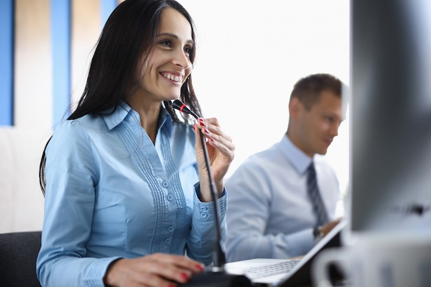 Business woman in office talking on conference call through microphone.