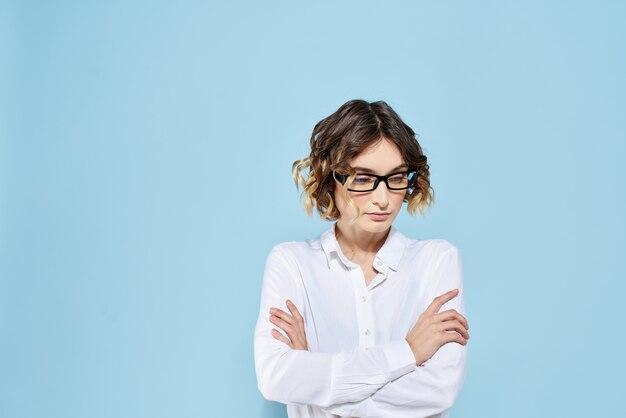 暗い縁の巻き毛の青い眼鏡のビジネスウーマンライトシャツのクロップドビュー。