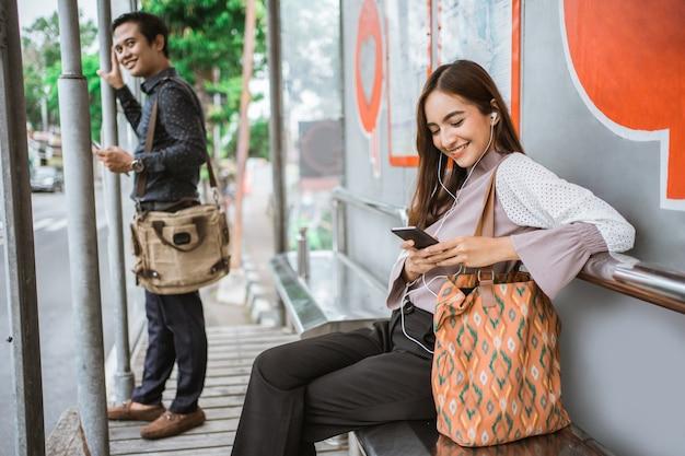 Деловая женщина на автовокзале в ожидании автобуса во время разговора по телефону