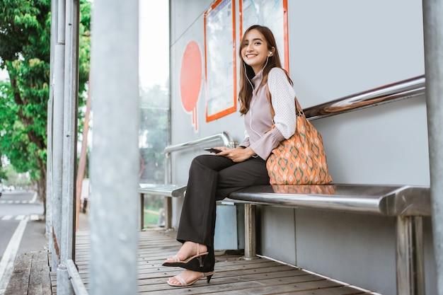 Деловая женщина на автобусной станции в ожидании автобуса