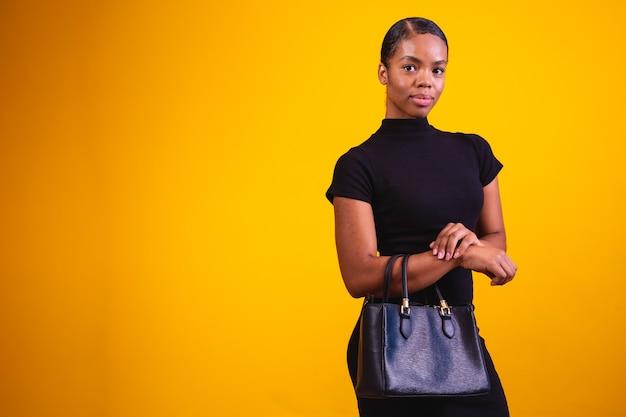 검은 옷과 손 가방을 입고 노란색 배경에 비즈니스 여자.