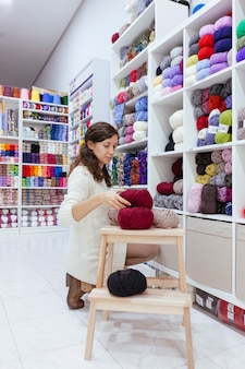 Business woman organizing wool yarns at her own enterprise of woollen yarns