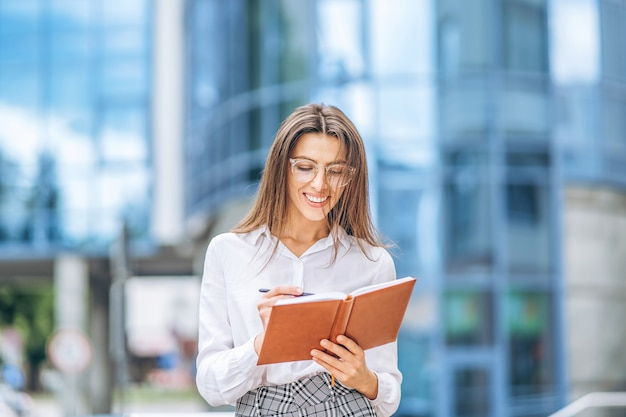 Business woman outdoors near modern business center with notebook.