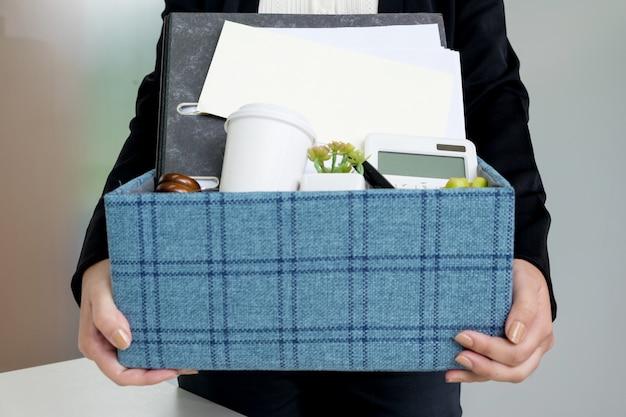 그녀가 사직을 결정하고 미래에 일을 바꿀 때 개인 회사 소지품을 포장하는 비즈니스 우먼