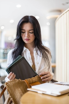 Business woman packing tablet cosmetics documents into handbag