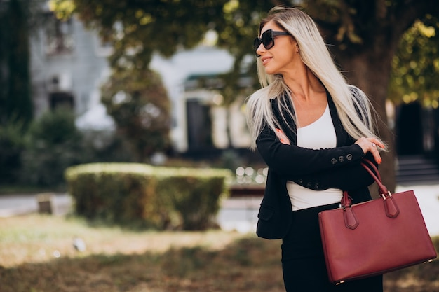 Business woman in park with red bag