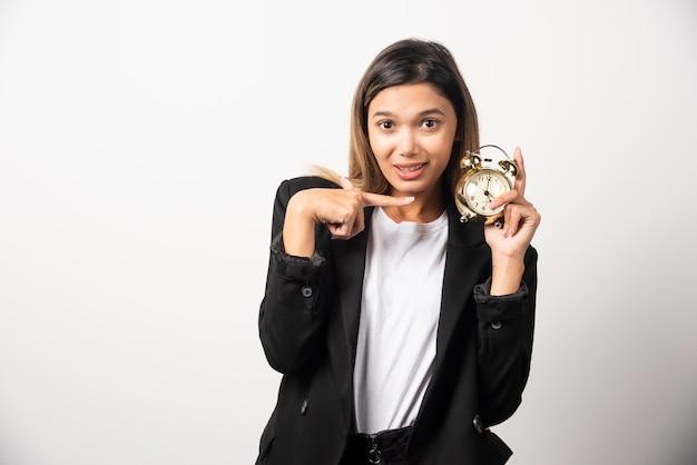 흰 벽에 알람 시계를 가르키는 비즈니스 여자.