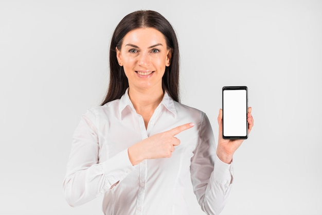 Business woman pointing finger at smartphone with blank screen