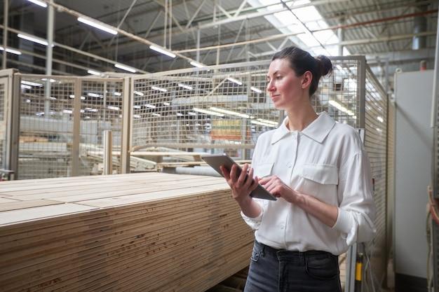 Портрет деловой женщины на столярной фабрике с помощью планшетного пк