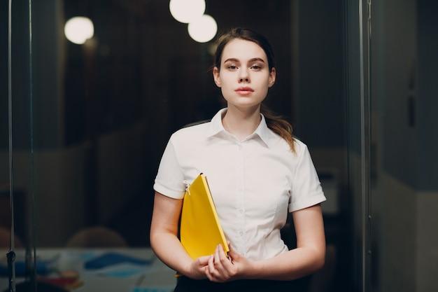 Деловой портрет женщины в белой рубашке стоит в офисе