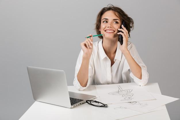 Деловая женщина позирует изолированно над серой стеной, сидя за столом, используя рисунок ноутбука и разговаривая по телефону