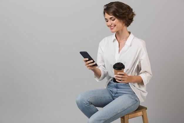 Деловая женщина позирует изолированно над серой стеной, сидя на стуле, используя портативный компьютер, разговаривая по телефону