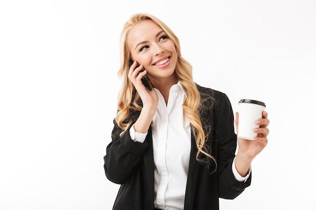 ビジネスの女性が電話で話しているコーヒーカップを保持している白い壁に孤立したポーズします。